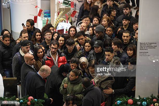 Customers wait to board an escalator at Selfridges on Oxford Street as the department store opens for its Boxing Day sale on December 26 2016 in...