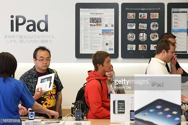 Customers wait to purchase Apple iPad tablet computers at the Apple Store Ginza on the day of its Japanese launch on May 28 2010 in Tokyo Japan The...