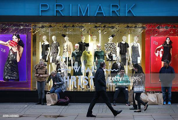 Customers wait with their purchases outside Primark's flagship store on Oxford Street on November 5 2014 in London England Retail giant Marks and...