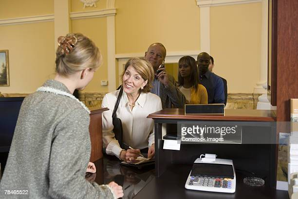 Customers waiting for bank teller