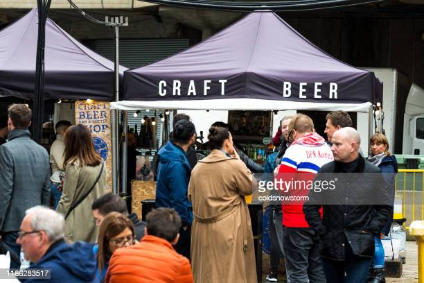 customers waiting in line at craft beer stall at food market - greater london stock pictures, royalty-free photos & images