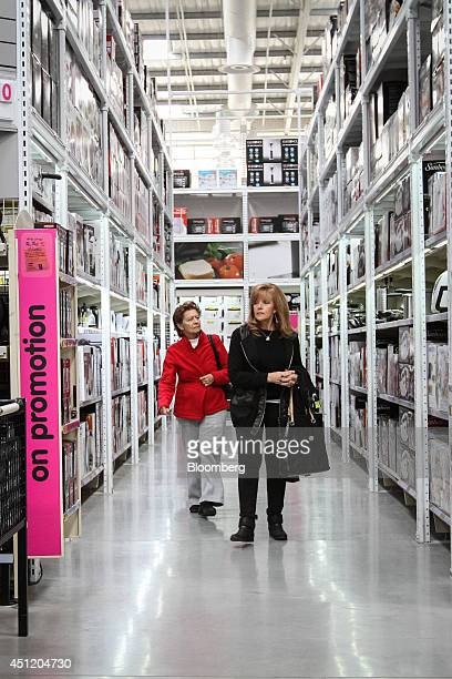 Customers walk along an aisle stocked with homewares inside a Makro cash and carry store operated by Massmart Holdings Ltd in Alberton South Africa...