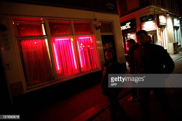 Customers walk around the redlightdistrict windows in the 'wallen' redlight district of Amsterdam on November 15 the Netherlands Twins Martine and...