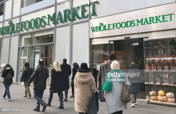 Customers walk into a Whole Foods Market store in New York on Nov 15 2017 Amazoncom Inc the owner of the grocery store chain announced the same day...