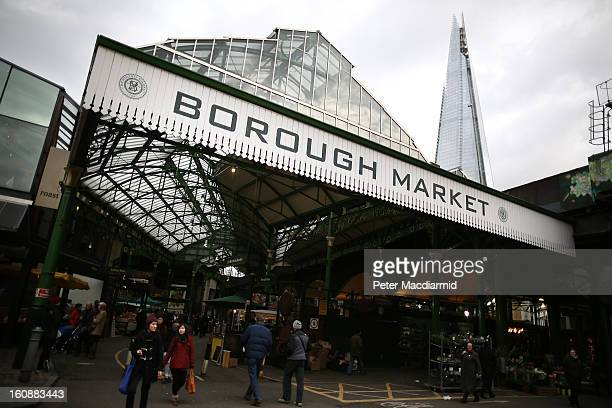 Customers walk into Borough Market in sight of The Shard skyscraper on February 7 2013 in London England Borough Market London's oldest since 1756...