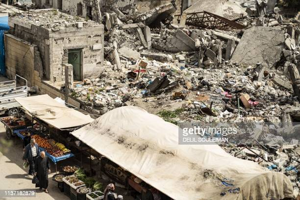 Customers walk near make-shift fruit and vegetable shops set in front of destroyed buildings in the northern Syrian city of Raqa, the former Syrian...