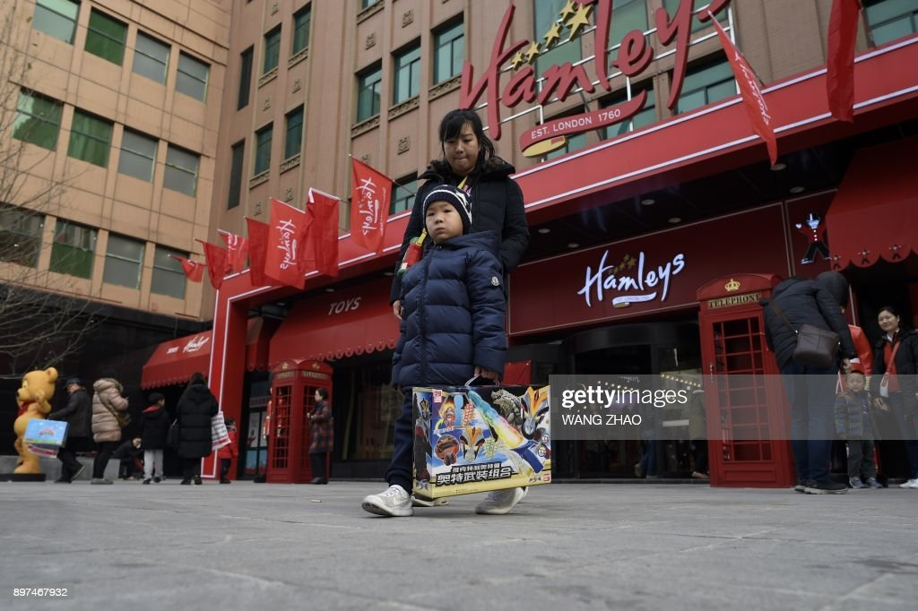 Customers walk out after shopping on the opening day of a new Hamleys store, the iconic British toy retailer now Chinese-owned, in Beijing on December 23, 2017. The well-loved British toy retailer, which was sold to a Chinese company in 2015, first opened in 1760 and has been expanding internationally, opening stores in locations ranging from Moscow to Dubai. /