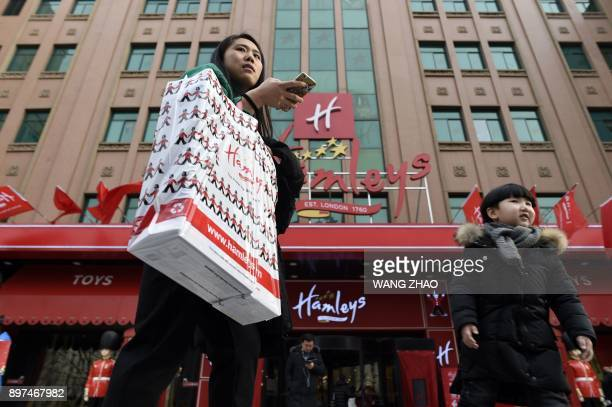 Customers walk out after shopping on the opening day of a new Hamleys store the iconic British toy retailer now Chineseowned in Beijing on December...