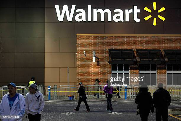 Customers walk outside WalMart Thanksgiving day on November 28 2013 in Troy Michigan Black Friday shopping began early this year with most major...