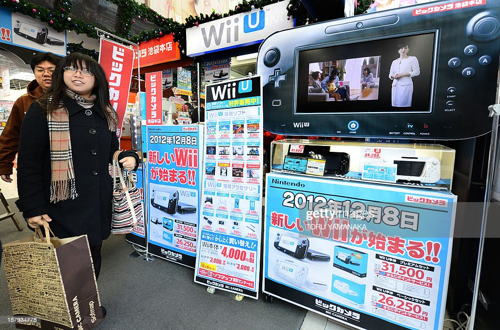 Customers walk past a console display (R) after purchasing Japanese electronics titan Nintendo's new videogame console 'Wii U' at a shop in Tokyo on December 8, 2012. Nintendo released the new console in Japan on December 8 and is hoping for a repeat of the runaway success it had with original Wii consoles, which lured legions of 'casual gamers' into the videogame world with the introduction of motion-sensing controls. AFP PHOTO/Toru YAMANAKA