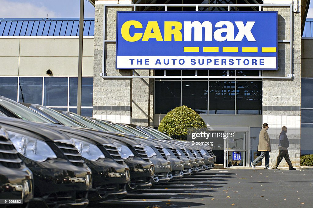 Customers walk past a row of cars for sale at Carmax in Norc ...