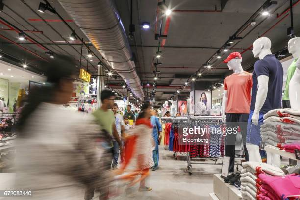 Customers walk past clothes on display at a Big Bazaar hypermarket operated by Future Retail Ltd in Mumbai India on Sunday April 16 2017 Future...