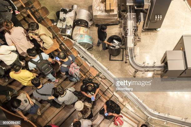 Customers walk past coffee beanpackaging equipment inside the Starbucks Corp Reserve Roastery store in Shanghai China on Friday May 11 2018...