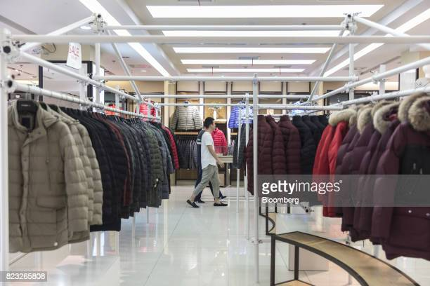 Customers walk past down jackets displayed inside the Bosideng International Holdings Ltd. Flagship clothing store in Shanghai, China, on Friday,...