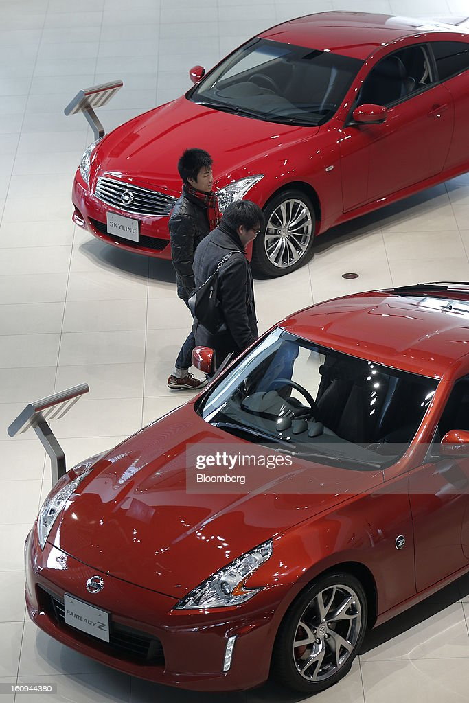 Customers walk past Nissan Motor Co. Fairlady Z, front, and Skyline vehicles displayed at the company's showroom in Yokohama, Kanagawa Prefecture, Japan, on Friday, Feb. 8, 2013. Nissan, Japan's second-biggest carmaker, reported third-quarter profit that fell short of analysts' estimates, after sales tumbled in China and new models trailed competitors in the U.S. Photographer: Kiyoshi Ota/Bloomberg via Getty Images