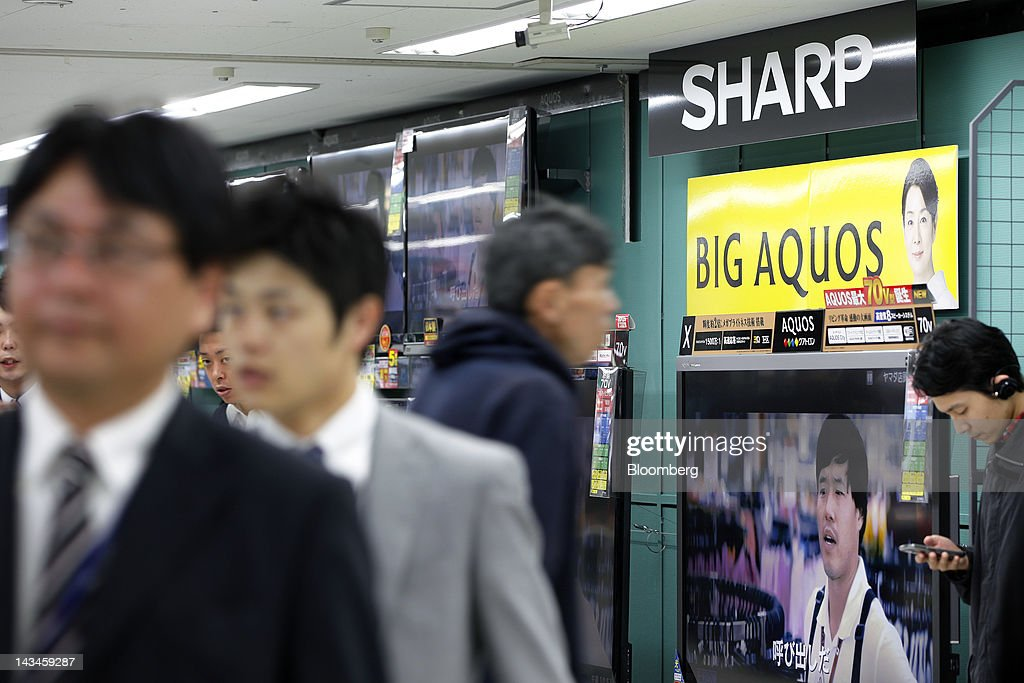 Customers walk past Sharp Corp. Aquos liquid crystal display (LCD) televisions at the Labi Ofuna electronics store, operated by Yamada Denki Co., in Yokohama City, Kanagawa Prefecture, Japan, on Friday, April 27, 2012. Sharp Corp., Japan's biggest maker of LCD panels, forecast a net loss wider than analyst estimates as falling TV prices prompted the company to turn to Foxconn Technology Group for investment. Photographer: Kiyoshi Ota/Bloomberg via Getty Images