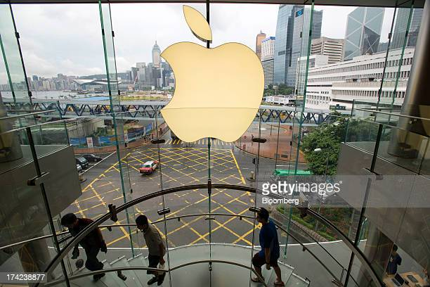 Customers walk up a staircase inside an Apple Inc store in Hong Kong China on Tuesday July 16 on Tuesday July 16 2013 Apple Inc is expected to...