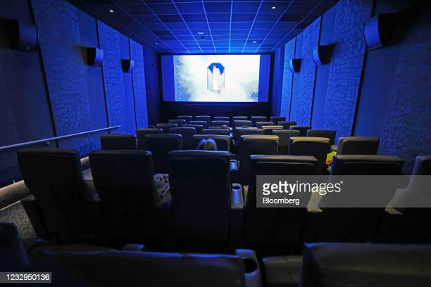 Customers watch a screen inside the Odeon cinema in Leicester Squaure in London, U.K., on Monday, May 17, 2021. England progresses to its third step...
