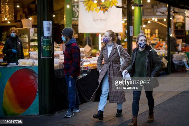 Customers wear face masks because of the coronavirus pandemic as they shop at Borough Market in London on January 12, 2021. - Borough market, an...