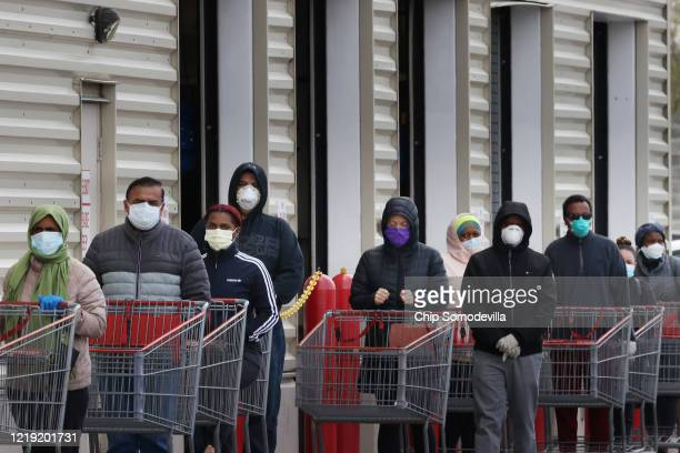 Customers wear face masks to prevent the spread of the novel coronavirus as they line up to enter a Costco Wholesale store April 16, 2020 in Wheaton,...