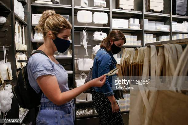 Customers wear face masks while shopping at a Muji store in Islington on July 11, 2020 in London, England. On Friday, Scotland made it mandatory to...