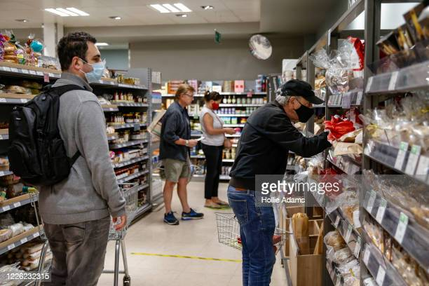Customers wear face masks while shopping at Waitrose in Islington on July 11, 2020 in London, England. On Friday, Scotland made it mandatory to wear...