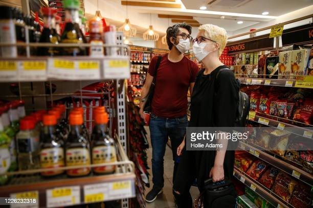 Customers wear face masks while shopping in Islington on July 11, 2020 in London, England. On Friday, Scotland made it mandatory to wear face...