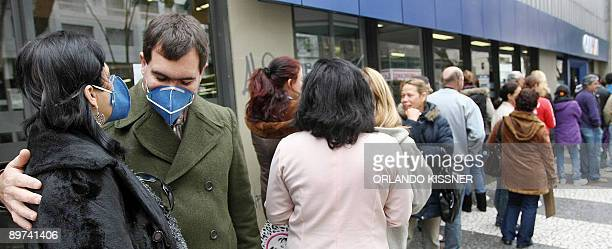 Customers wear surgical masks to combat the influenza A as they queue outside a bank following a decision of the Labour Ministry to limit to 10 the...