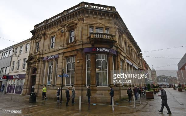 Customers, wearing a face mask or covering due to the COVID-19 pandemic, socially distance as they queue to enter a NatWest bank in Blackburn, north...