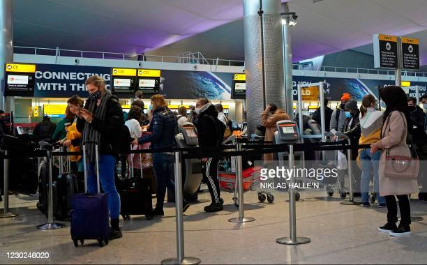 Customers wearing face covers queue at a TAP Air Portugal check-in desk in the departures hall at Terminal 2 of Heathrow Airport in west London on...