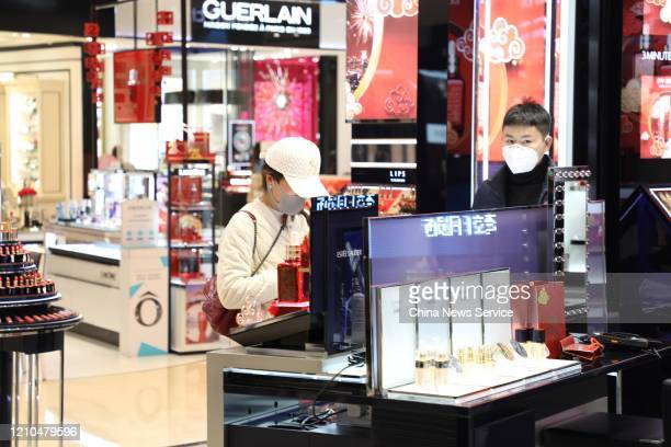 Customers wearing face masks select goods at a shop mall on March 4 2020 in Hangzhou Zhejiang Province of China A shopping mall in Hangzhou starts...