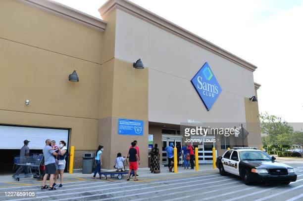 Customers wearing face masks wait in line to enter a Sam's Club store on July 16, 2020 in Miramar, Florida. Some major U.S. Corporations are...