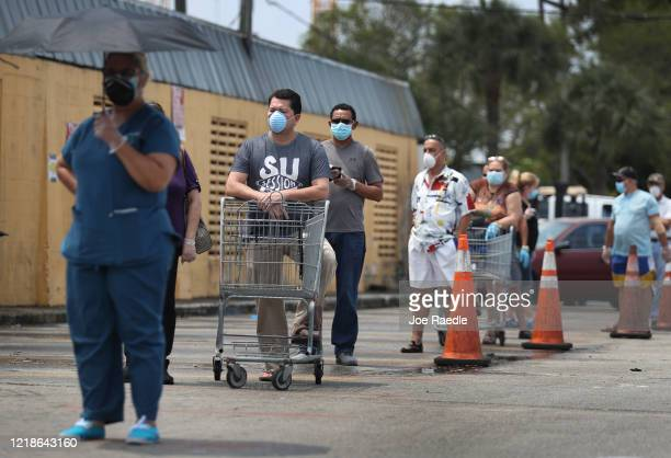Customers wearing masks line up to shop at the Presidente Supermarket on April 13, 2020 in Miami, Florida. The employees at Presidente Supermarket,...