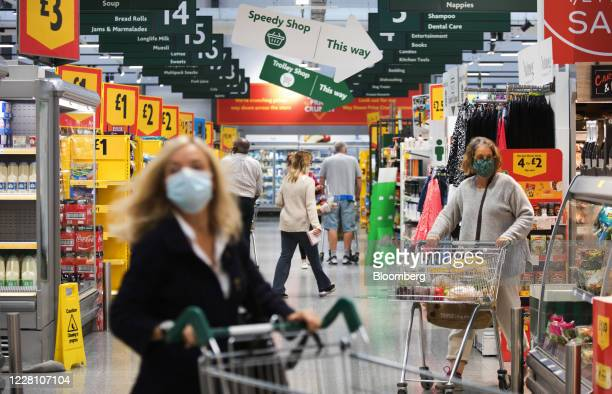 Customers wearing protective face masks pass along the main thoroughfare inside a Morrisons supermarket, operated by Wm Morrison Supermarkets Plc, in...