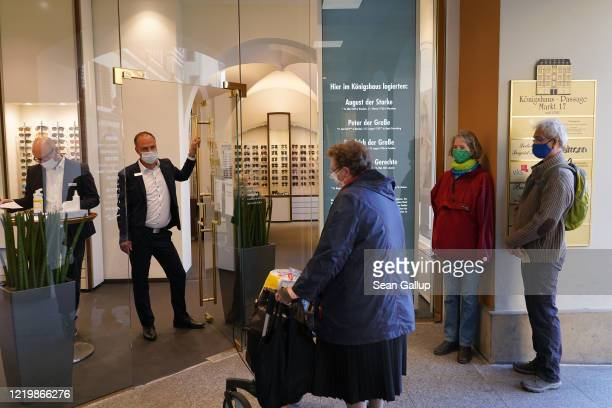 Customers wearing protective face masks prepare to enter a reopened opticians' for the first time since March on the first day of the easing of some...