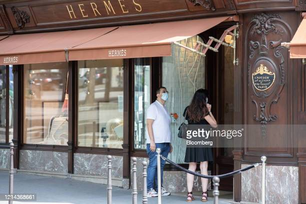Customers wearing protective face masks queue to enter a Hermes luxury goods boutique on George V Avenue in Paris France on Thursday May 21 2020...