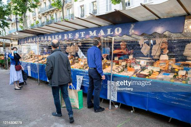Customers wearing protective face masks shop for seafood behind plastic customer facing screens at Marche SaxeBreteuil in Paris France on Thursday...