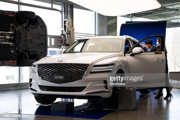 Customers wearing protective masks look at a Hyundai Motor Co. Genesis GV80 sport utility vehicle at the company's Motorstudio showroom in Seoul,...