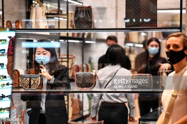 Customers wearing protective masks shop at the Galeries Lafayette on the first day of the reopening of the luxury general store, on May 30 in Paris,...