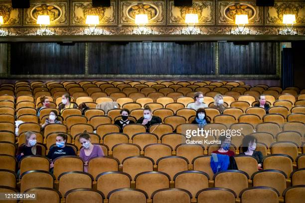 Customers wearing protective masks sit apart in observance of social distancing measures inside a movie theater as the Czech government lifted more...