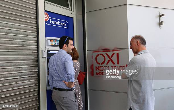 Customers withdraw cash from an automated teller machine beside an 'OXI' graffiti sign outside a Eurobank Ergasias SA bank branch in Athens Greece on...