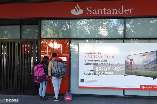 Customers withdraw cash from an automated teller machine operated by Santander bank in Madrid. Banco Santander will close another 411 bank branches...