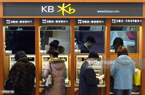 Customers withdraw cash from automatic teller machines at a Kookmin Bank business center in Seoul South Korea Thursday February 3 2005 South Korea's...