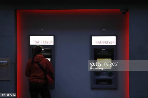 A customers withdraws cash from an automated teller machine outside a Raiffeisen Schweiz Genossenschaft bank branch in Bern Switzerland on Tuesday...