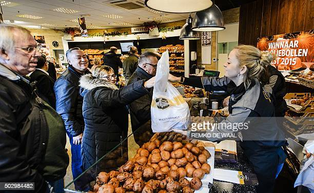 Customes buy 'oliebollen' by donutmaker Richard Visser on December 31 2015 in Spijkernisse An oliebol is a donutlike product traditionally made and...