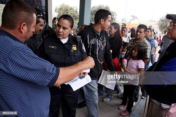 Customs Agent A Fogg facing camera answers questions for citizens waiting in line to file for passports at the San Ysidro Community Centeron on May...