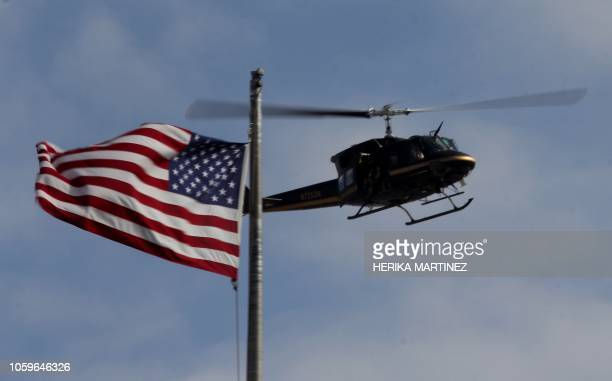 A US customs and border patrol helicopter overflies a US flag in El Paso Texas at the USMexico border during a crowd control drill as seen from...