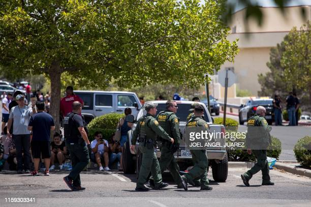 Customs and Border Patrol police walk past individuals that were evacuated from Cielo Vista Mall and a WalMart where a shooting occurred in El Paso...