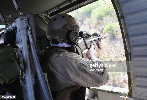 S Customs and Border Protection agent aims his weapon from a Black Hawk helicopter while pursuing a truck with suspected undocumented immigrants on...