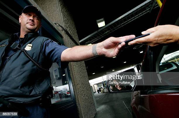 Customs and Border Protection agent Bob Schulze checks a passport at the vehicle crossing at the San Ysidro Port of Entry June 1 2009 in San Ysidro...